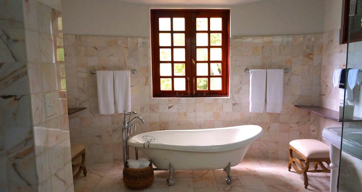 a stylish bathroom showinga free standing bath and a garden scene though the window
