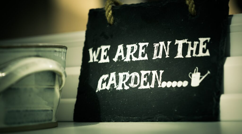 small blackboard with the words 'we are in the garden' written in chalk