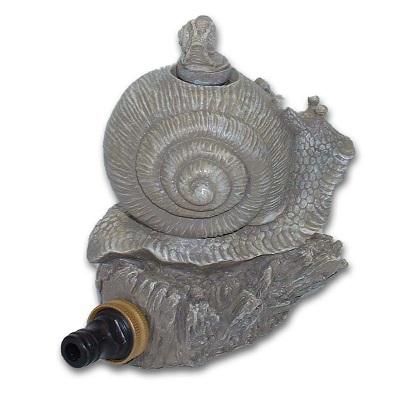 A garden sprinkler in the shape of a snail sitting on a rock.