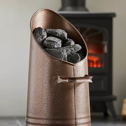 copper coal hod filled with coal stands in front of a coal fire