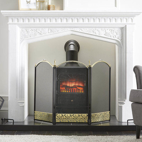 uk wholesale fire screen, finished in black and brass stands in front of a fire stove