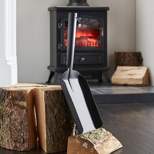 uk wholesale fireplace accessories shows a coal shovel leaning against some logs of wood in front of a fireplace.