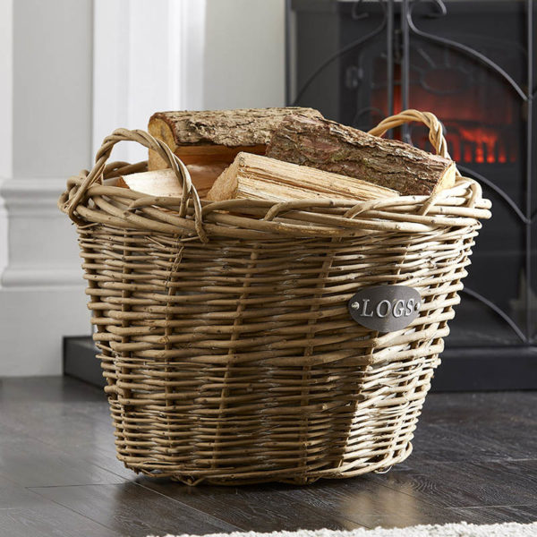 wholesale wicker log basket with handles filled with logs stand in front of a lit stove fire