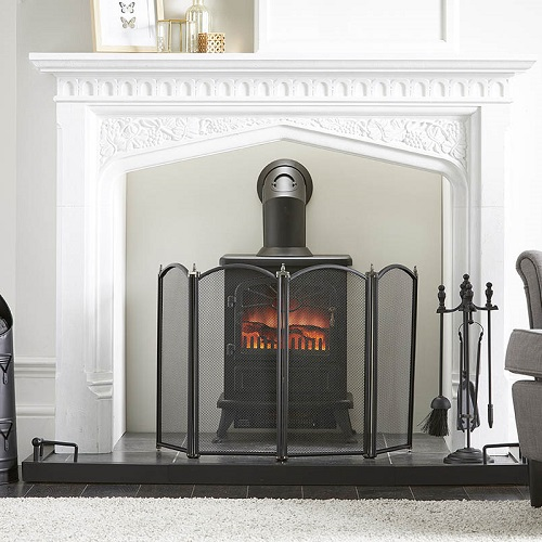 Fireplace starter set showing a black spark guard and companion set arranged in front of a stove fire