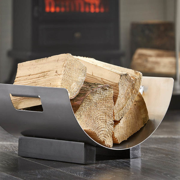 wholesale ironware log basket with a curved design is shown holding logs in front of a stove fire