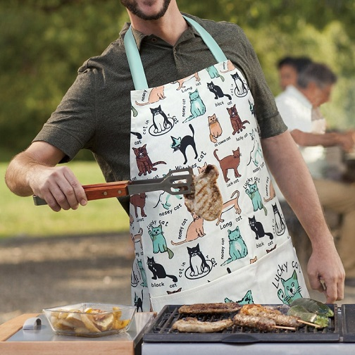 Man in a coking apron stood in front of a barbique
