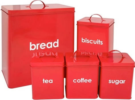 A collection of metal kitchen containers painted red including bread, biscuits, tea, coffee and sugar